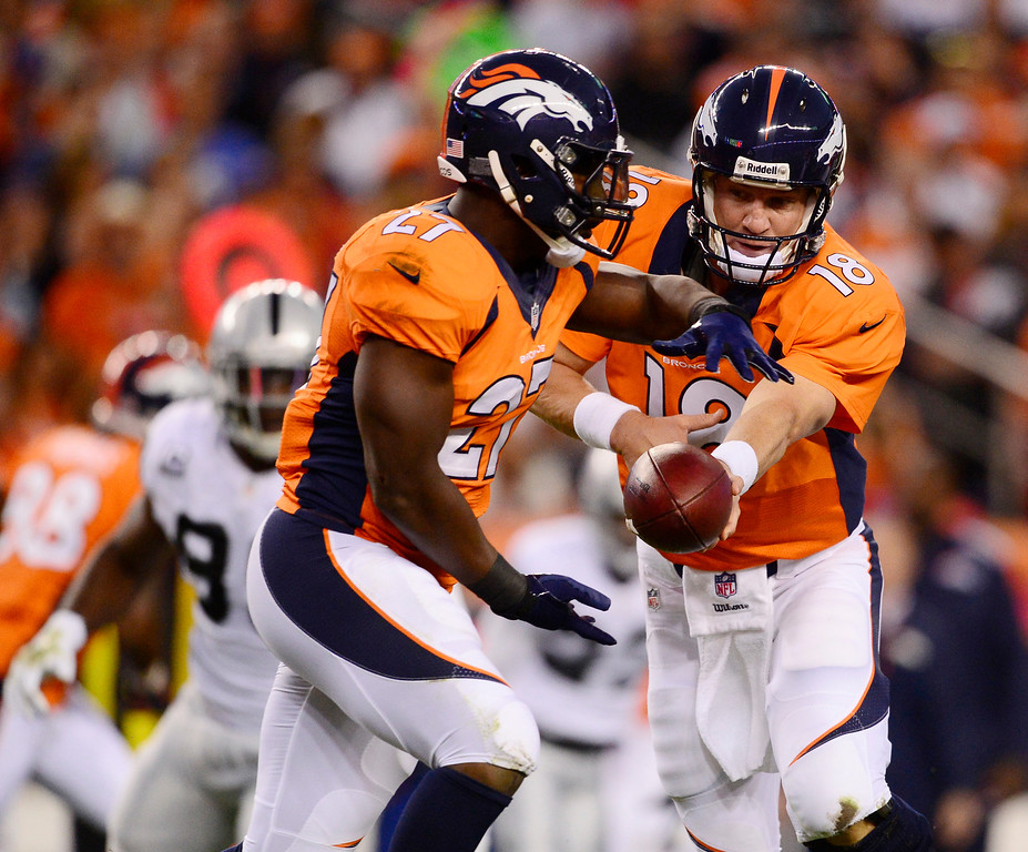 Description of . Denver Broncos quarterback Peyton Manning (18) hands off to Denver Broncos running back Knowshon Moreno (27) in the first quarter. The Denver Broncos took on the Oakland Raiders at Sports Authority Field at Mile High in Denver on September 23, 2013. (Photo by AAron Ontiveroz/The Denver Post)