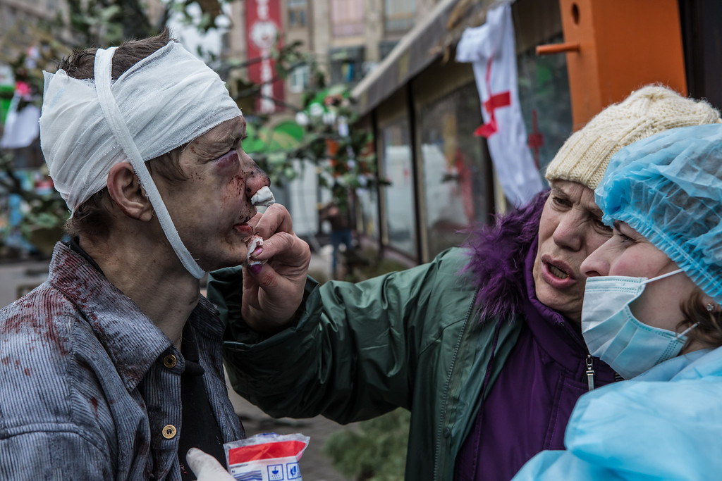 Description of . A wounded anti-government protester is treated by medics near Independence Square on February 20, 2014 in Kiev, Ukraine. After several weeks of calm, violence has again flared between anti-government protesters and police, with dozens killed. (Photo by Brendan Hoffman/Getty Images)