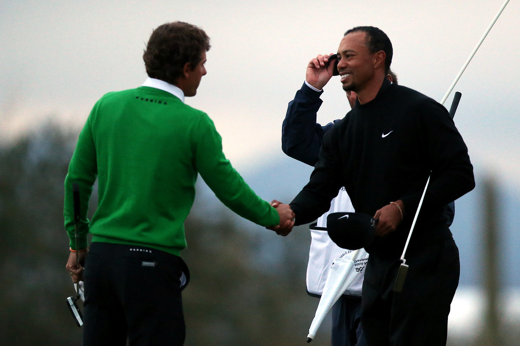 Description of . MARANA, AZ - FEBRUARY 21:  (L-R) Charles Howell III is congratulaed by Tiger Woods after Howell won their match 2 and 1 in 17 holes during the first round of the World Golf Championships - Accenture Match Play at the Golf Club at Dove Mountain on February 21, 2013 in Marana, Arizona. Round one play was suspended on February 20 due to inclimate weather and is scheduled to be continued today.  (Photo by Jed Jacobsohn/Getty Images)