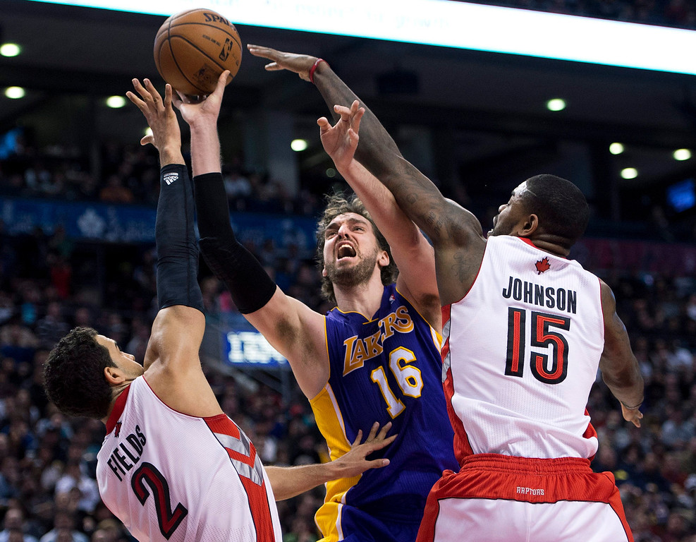 Description of . Toronto Raptors' Landry Fields (2) and Amir Johnson (15) battles for the ball against Los Angeles Lakers' Pau Gasol (16) during the second half of an NBA basketball game, Sunday, Jan. 20, 2013, in Toronto. The Raptors won 108-103. (AP Photo/The Canadian Press, Nathan Denette)