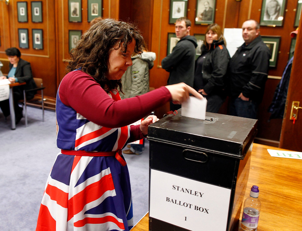 Description of . Falkland Islander Joan Turner, wearing a dress with the Union Jack colours, casts her vote at the Town Hall polling station in Stanley, March 10, 2013. Residents of the Falkland Islands started voting on Sunday in a sovereignty referendum that seeks to counter Argentina's increasingly assertive claim over the British-ruled territory. REUTERS/Marcos Brindicci