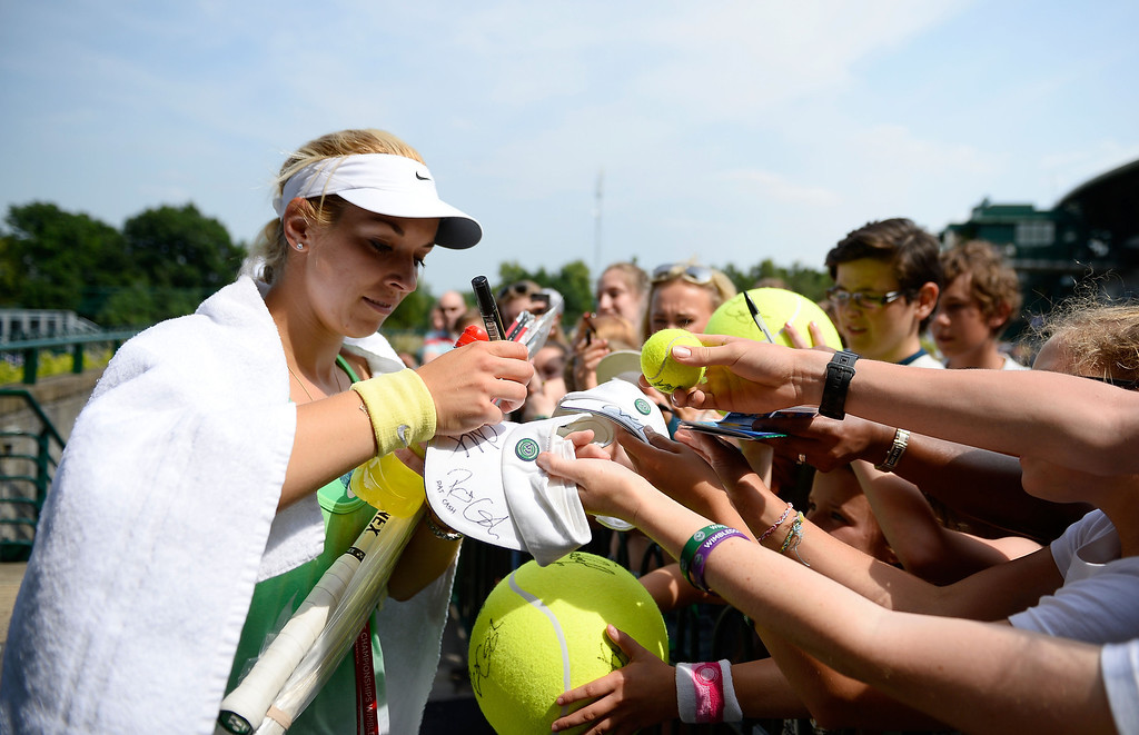 Description of . LONDON, ENGLAND - JULY 05:  Sabine Lisicki of Germany signs autographs for fans after a practice session on day eleven of the Wimbledon Lawn Tennis Championships at the All England Lawn Tennis and Croquet Club on July 5, 2013 in London, England.  (Photo by Dennis Grombkowski/Getty Images)
