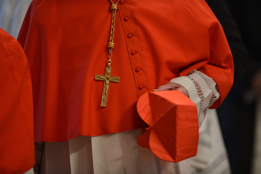 Description of . A cardinal holds his berretta during a mass at the St Peter\'s basilica before the conclave on March 12, 2013 at the Vatican. AFP PHOTO / GABRIEL BOUYS/AFP/Getty Images