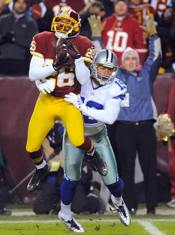. Washington Redskins cornerback Josh Wilson (26) makes the catch for an interception in front of Dallas Cowboys wide receiver Miles Austin (19) during the first half of an NFL football game Sunday, Dec. 30, 2012, in Landover, Md. (AP Photo/Richard Lipski)