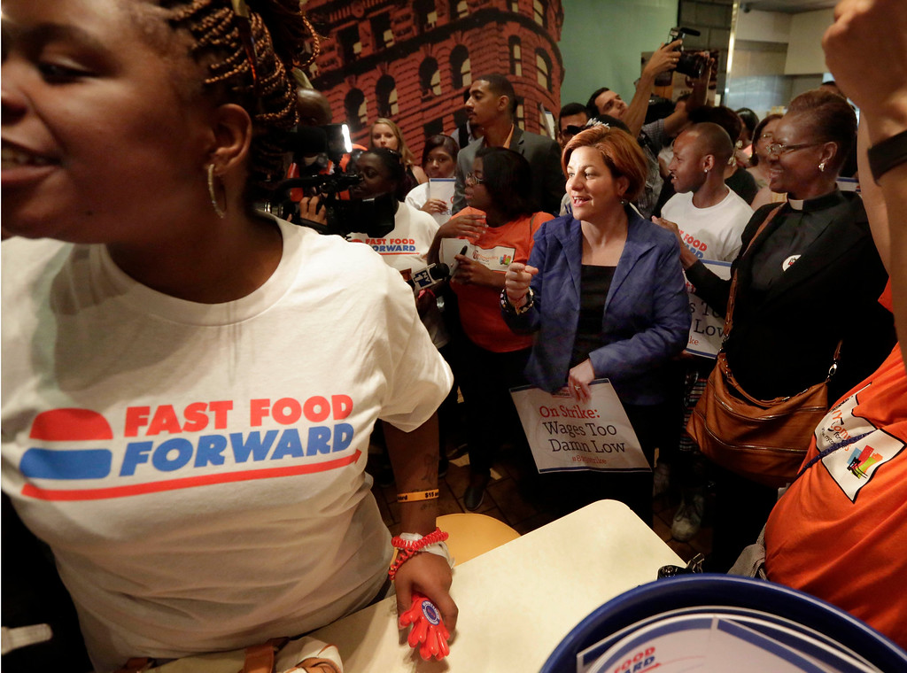 Description of . Protesting fast food workers, joined by New York City Council Speaker and mayoral candidate Christine Quinn, center, and protest organizers, occupy a McDonald's restaurant on New York's Fifth Avenue, Thursday, Aug. 29, 2013. (AP Photo/Richard Drew)