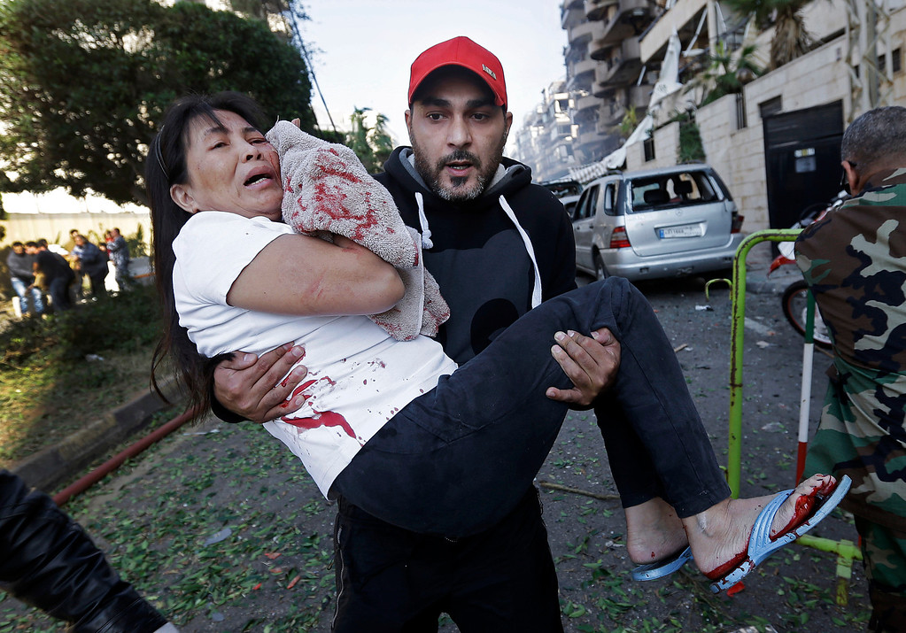 . A Lebanese man carries an injured Asian domestic worker, at the scene where two explosions have struck near the Iranian Embassy killing many, in Beirut, Lebanon, Tuesday Nov. 19, 2013. (AP Photo/Hussein Malla)