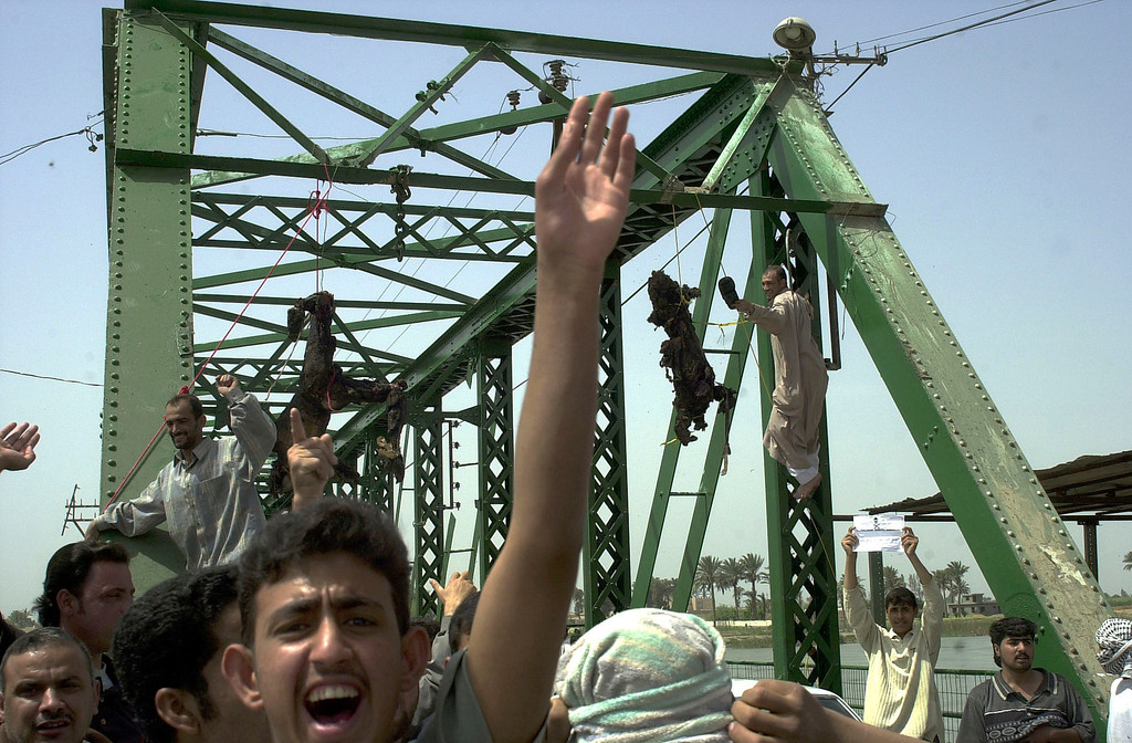 . Iraqis chant anti-American slogans as charred bodies hang from a bridge over the Euphrates River in Fallujah, west of Baghdad, Wednesday, March 31 2004. Enraged Iraqis killed four foreigners, including at least one U.S. national, took the charred bodies from a burning SUV, dragged them through the streets, and hung them from the bridge. (AP Photo/Khalid Mohammed)