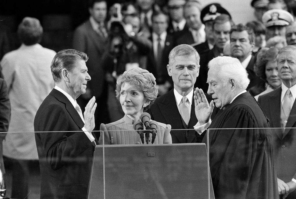 Description of . President Ronald Reagan takes the oath of office as First Lady Nancy Reagan looks on in 1981 in Washington, DC. (AP Photo)