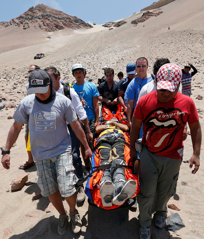 Description of . Medics, helped by fans, evacuate Leonardo Martinez of Bolivia who was injured after crashing with his quad in the 3nd stage of the 2013 Dakar Rally from Pisco to Nazca, Peru, Monday, Jan. 7, 2013. The race finishes in Santiago, Chile, on Jan. 20. (AP Photo/Victor R. Caivano)