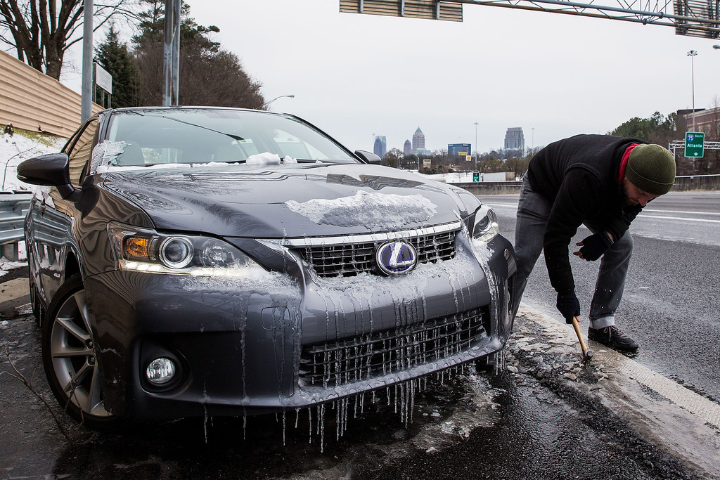 Description of . Joe Galunas works to clear ice and retrieve the car he abandoned on an exit ramp along I-75 North during the winter storm January 29, 2014 in Atlanta, Georgia.    (Photo by Daniel Shirey/Getty Images)