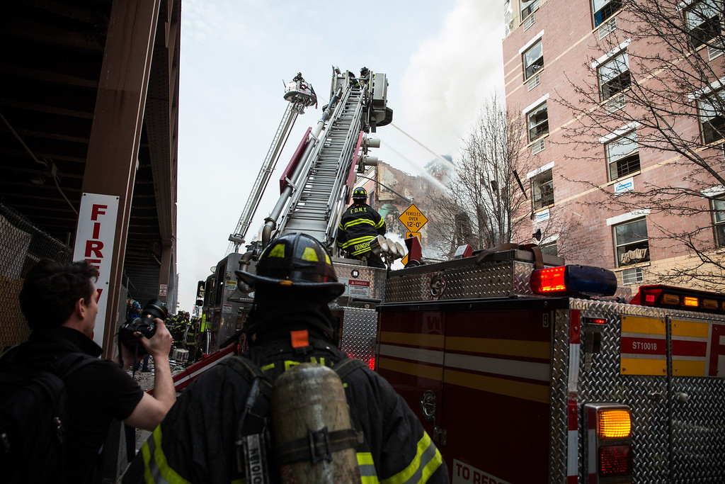 Description of . A ladder truck pours water as the Fire Department of New York (FDNY) respond to a 5-alarm fire and building collapse at 1646 Park Ave in the Harlem neighborhood of Manhattan March 12, 2014 in New York City. Reports of an explosion were heard before the collapse of two multiple-dwelling buildings that left at least 11 injured.  (Photo by Andrew Burton/Getty Images)
