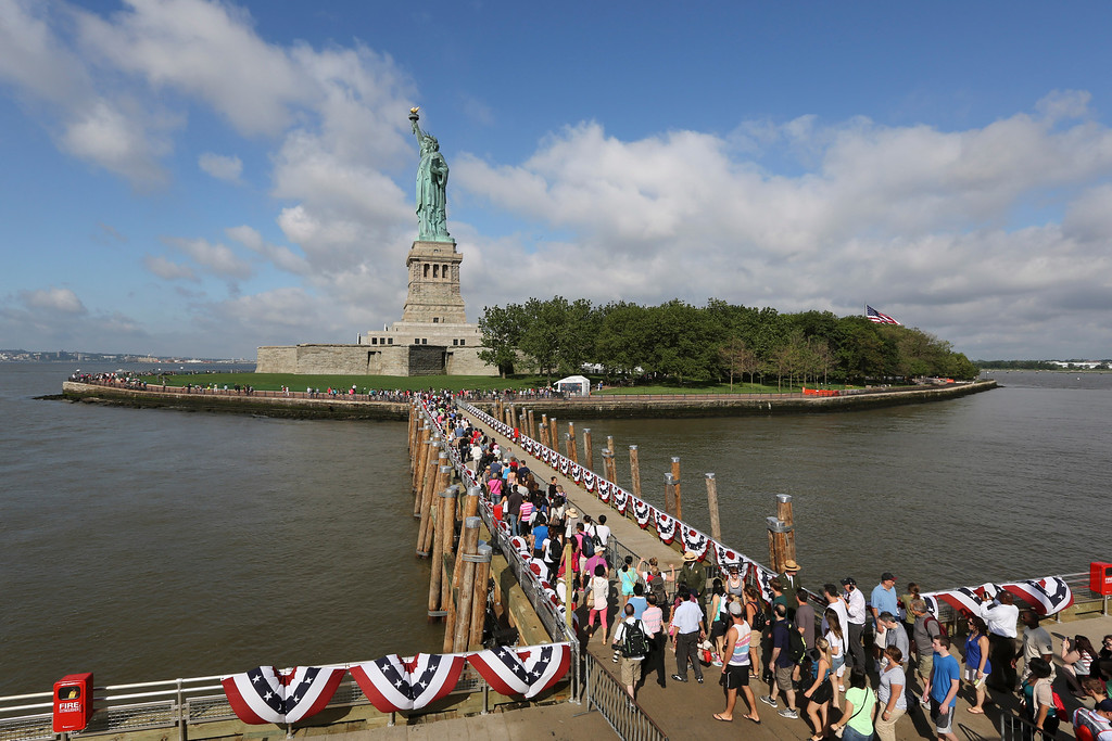 Description of . Visitors to the Statue of Liberty disembark onto Liberty Island from the first ferry to leave Manhattan, Thursday, July 4, 2013, in New York. The Statue of Liberty finally reopened on the Fourth of July months after Superstorm Sandy swamped its little island in New York Harbor as Americans across the country marked the holiday with fireworks and barbecues. (AP Photo/Mary Altaffer)