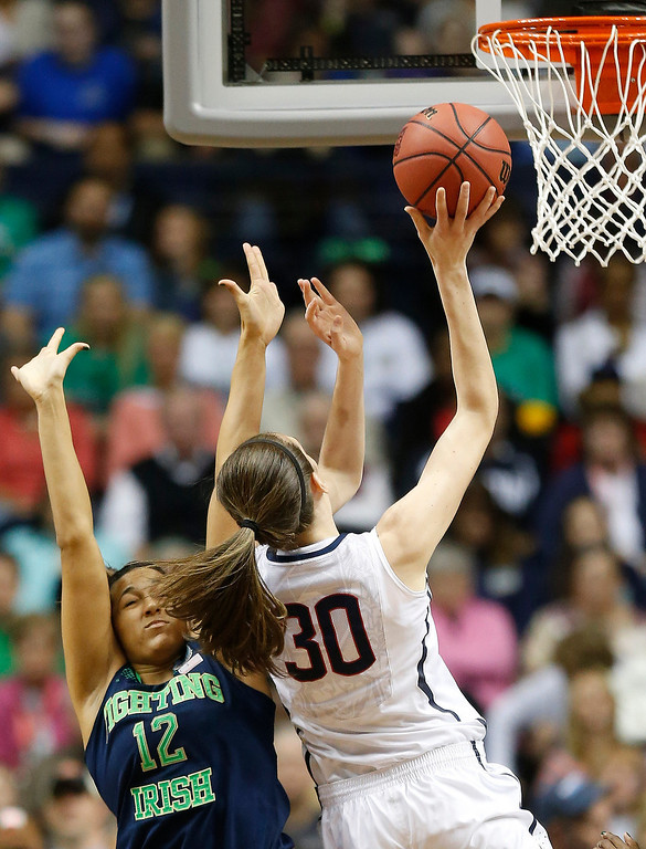 Description of . Connecticut forward Breanna Stewart (30) shoots against Notre Dame forward Taya Reimer (12) during the first half of the championship game in the Final Four of the NCAA women's college basketball tournament, Tuesday, April 8, 2014, in Nashville, Tenn. (AP Photo/John Bazemore)