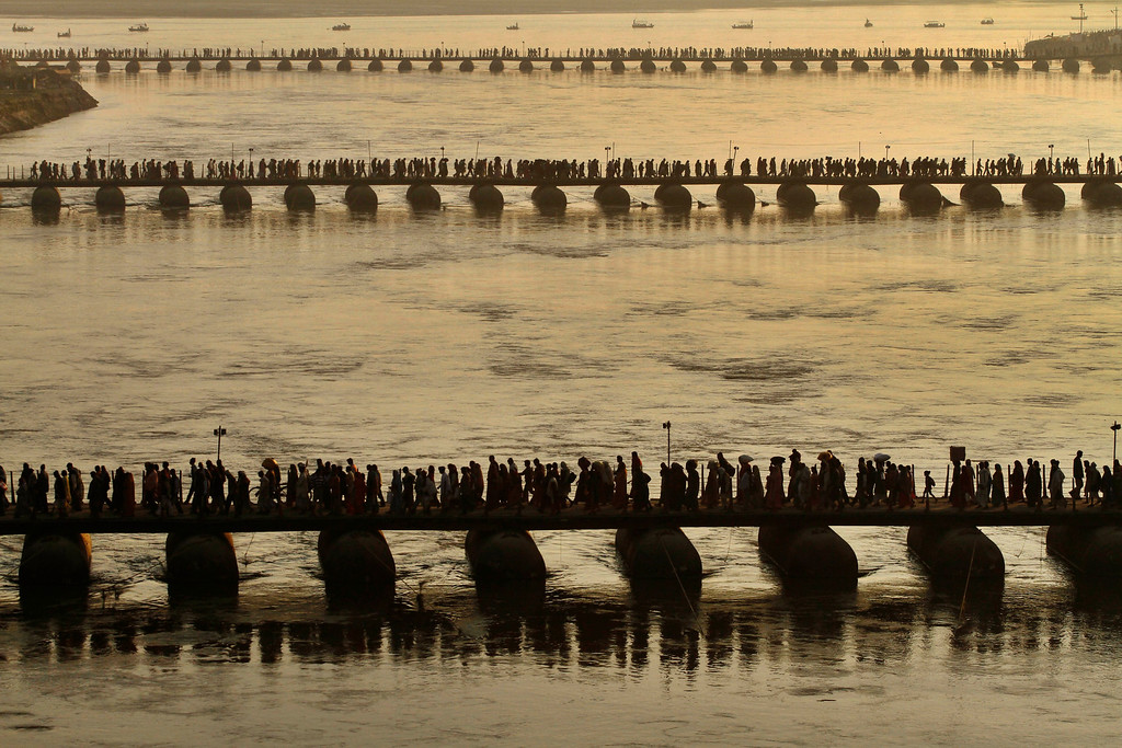 Description of . In this Jan. 22, 2012 file photo, Hindu devotees cross a newly constructed temporary bridge at Sangam, the confluence of rivers Ganges and Yamuna, in Allahabad, India. Hundreds of thousands of Hindu pilgrims take dips in the confluence, some hoping to wash away sins and others to secure a spouse, during the month long festival. (AP Photo/Rajesh Kumar Singh, File)