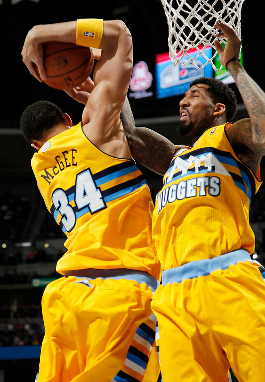 Description of . Denver Nuggets forwards JaVale McGee, left, and Wilson Chandler get tied up with each other on a rebound, against the Boston Celtics in the first quarter of an NBA basketball game in Denver on Tuesday, Feb. 19, 2013. (AP Photo/David Zalubowski)