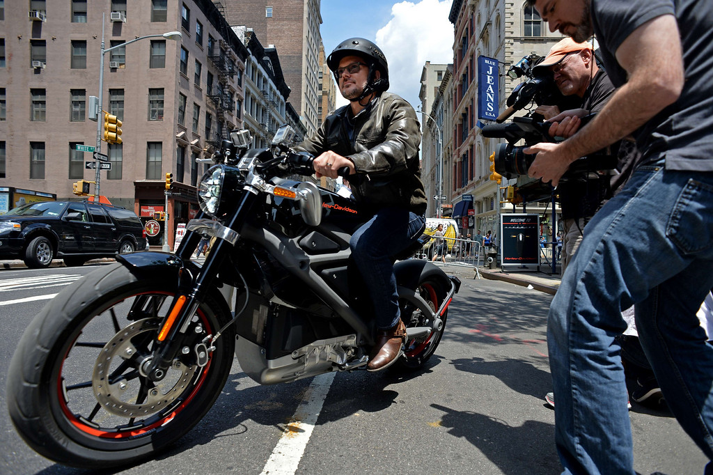 Description of . Harley-Davidson chief marketing officer Mark-Hans Richer takes a Project LiveWire, the company's first electric motorcycle, for a ride during a preview June 23, 2014 outside a Harley-Davidson dealer in New York. AFP PHOTO/Stan  HONDA/AFP/Getty Images