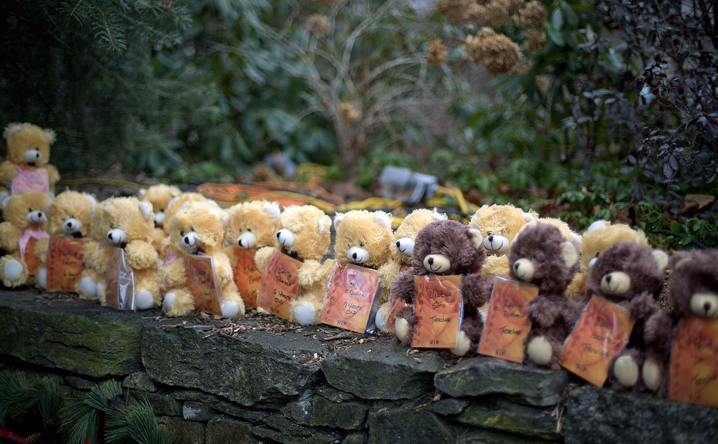 Description of . Teddy bears, each representing a victim of the Sandy Hook Elementary School shooting, sit on a wall at a sidewalk memorial, Sunday, Dec. 16, 2012, in Newtown, Conn. A gunman walked into Sandy Hook Elementary School in Newtown Friday and opened fire, killing 26 people, including 20 children. (AP Photo/David Goldman)