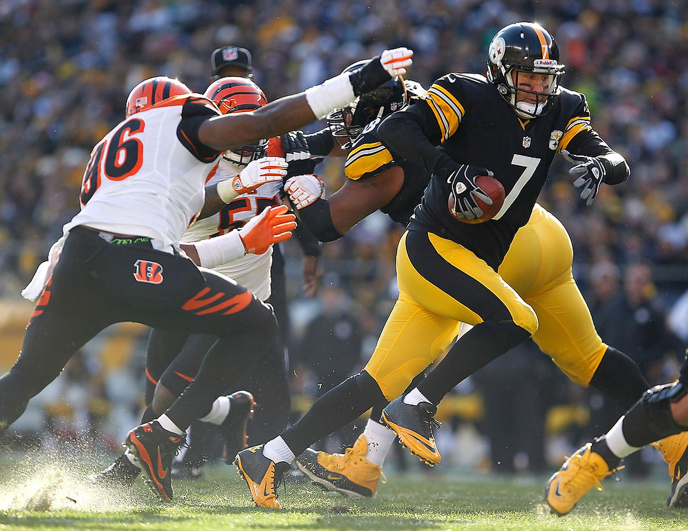 Description of . Ben Roethlisberger #7 of the Pittsburgh Steelers tries to outrun the tackle of Carlos Dunlap #96 of the Cincinnati Bengals during the second quarter at Heinz Field on December 23, 2012 in Pittsburgh, Pennsylvania. (Photo by Gregory Shamus/Getty Images)