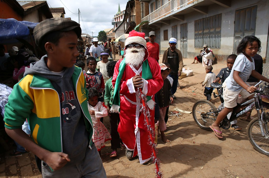 Description of . A Madagascar Father Chrismas walks in the dusty street of Ambohibary, 150km from Antananarivo, greeting children on December 25, 2013, days after Madagsacar went to th polls to vote  in a Presidential  election . Observers certified Madagascar's run-off presidential polls as free, credible and democratic on Sunday, urging bickering candidates to stay calm as counting continued after the vote to restore democracy.  ALEXANDER JOE/AFP/Getty Images