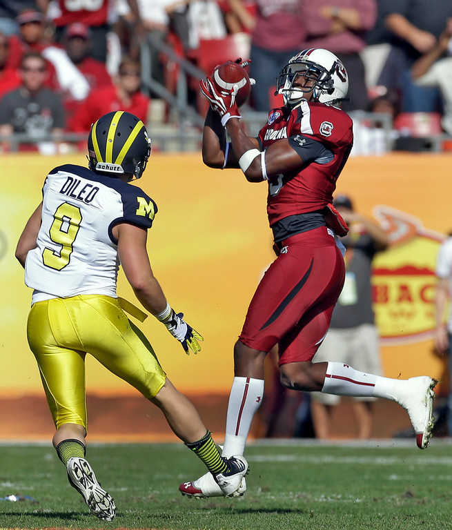 Description of . South Carolina cornerback Jimmy Legree (15) intercepts a pass intended for Michigan wide receiver Drew Dileo (9) during the first quarter of the Outback Bowl NCAA college football game, Tuesday, Jan. 1, 2013, in Tampa, Fla. (AP Photo/Chris O'Meara)