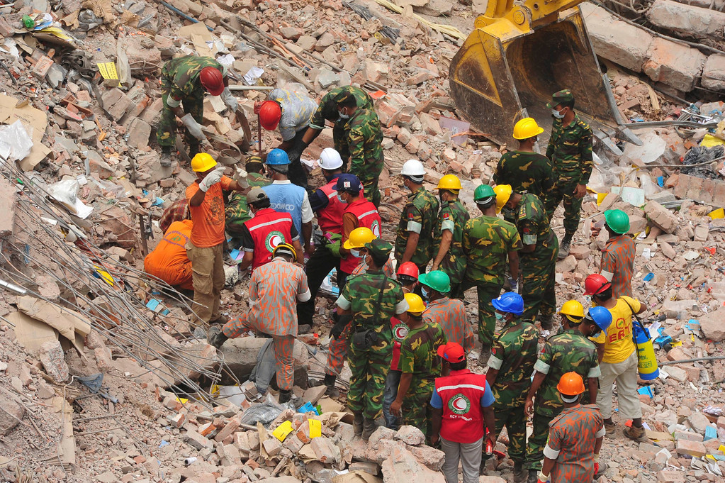 Description of . Rescue workers attempt to find survivors from the rubble of the collapsed Rana Plaza building in Savar, around 30 km (19 miles) outside Dhaka April 30, 2013.  REUTERS/Khurshed Rinku