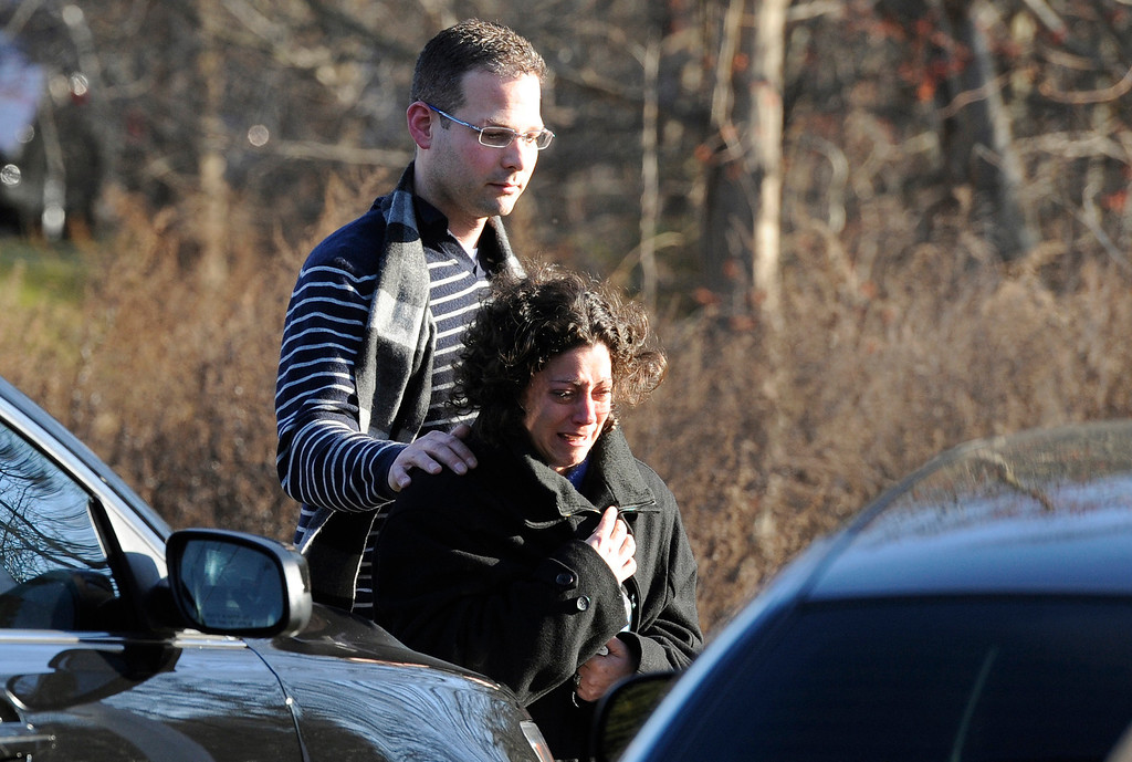 Description of . A man and woman leave the staging area for family around near the scene of a shooting at the Sandy Hook Elementary School in Newtown, Conn., about 60 miles (96 kilometers) northeast of New York City, Friday, Dec. 14, 2012. An official with knowledge of Friday's shooting said 27 people were dead, including 18 children.  (AP Photo/Jessica Hill)