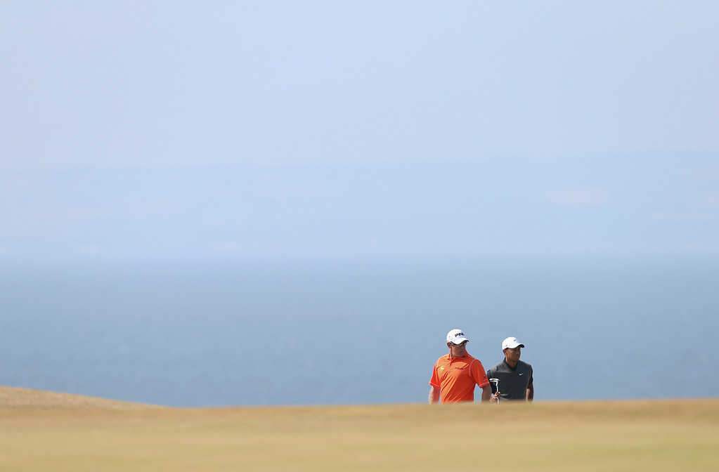 Description of . Tiger Woods of the United States, right, and Lee Westwood of England stand on the 5th fairway during the third round of the British Open Golf Championship at Muirfield, Scotland, Saturday July 20, 2013. (AP Photo/Scott Heppell)