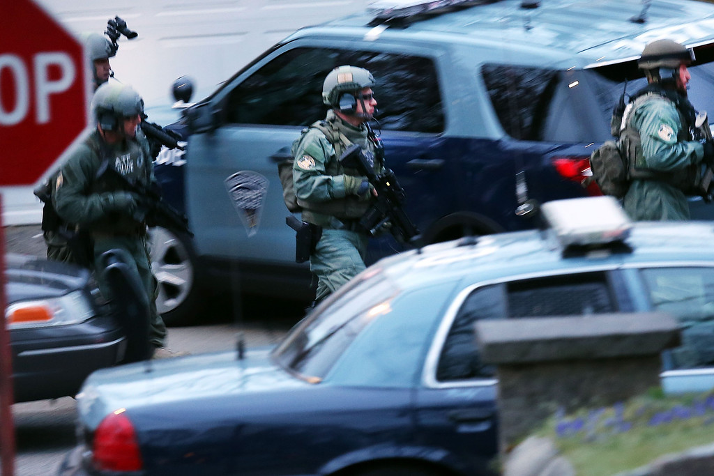 Description of . WATERTOWN, MA - APRIL 19:  Members of a police S.W.A.T. team run to the scene where it was believed 19-year-old bombing suspect Dzhokhar A. Tsarnaev  is in hiding on April 19, 2013 in Watertown, Massachusetts. After a car chase and shoot out with police, one suspect in the Boston Marathon bombing, Tamerlan Tsarnaev, 26, was shot and killed by police early morning April 19, and a manhunt is underway for his brother and second suspect, 19-year-old suspect Dzhokhar A. Tsarnaev. The two men, reportedly of Chechen origin, are suspects in the bombings at the Boston Marathon on April 15, that killed three people and wounded at least 170.  (Photo by Spencer Platt/Getty Images)