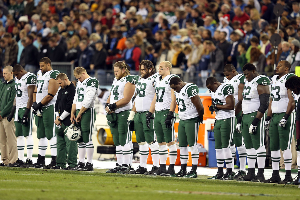 Description of . NASHVILLE, TN - DECEMBER 17:  The New York Jets stand on the sideline in a moment in silence for the victims of the mass shooting that took place at Sandy Hook elementary school in Newtown, Connecticut prior to the game against the Tennessee Titans at LP Field on December 17, 2012 in Nashville, Tennessee.  (Photo by Andy Lyons/Getty Images)