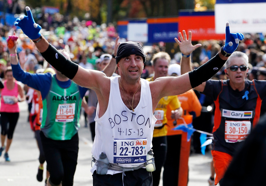 Description of . Wearing a shirt that pays tribute to victims of the Boston Marathon bombings, Andrew Mangone of the United  States reacts crossing the finish line after completing the New York City Marathon, Sunday, Nov. 3, 2013, in New York. (AP Photo/Kathy Willens)