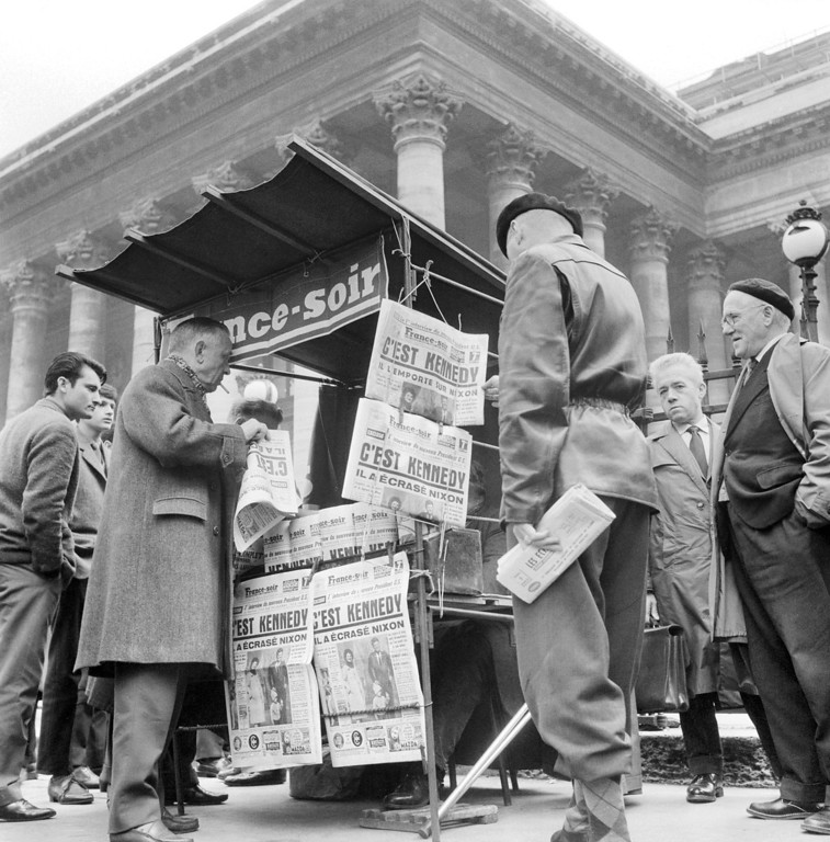 Description of . Parisians purchase newspapers that announce Kennedy as the new U.S. president Nov. 9, 1960.  AFP/Getty Images