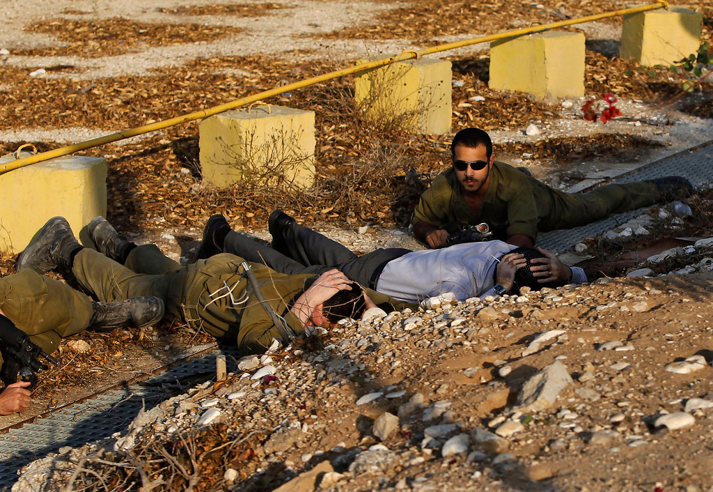 Description of . In this Nov. 20, 2012 file photo, Israeli soldiers and a civilian take cover as a siren alerting of an incoming rocket from Gaza Strip sounds in Ofakim, southern Israel. (AP Photo/Tsafrir Abayov, File)