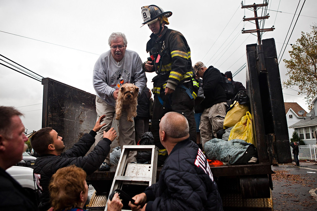 . A man hands a dog to first responders while being evacuated due to flood waters caused by Hurricane Sandy on October 30, 2012 in New York City. The storm has claimed at least 40 lives in the United States, and has caused massive flooding across much of the Atlantic seaboard. US President Barack Obama has declared the situation a \'major disaster\' for large areas of the US East Coast including New York City. (Photo by Andrew Burton/Getty Images)