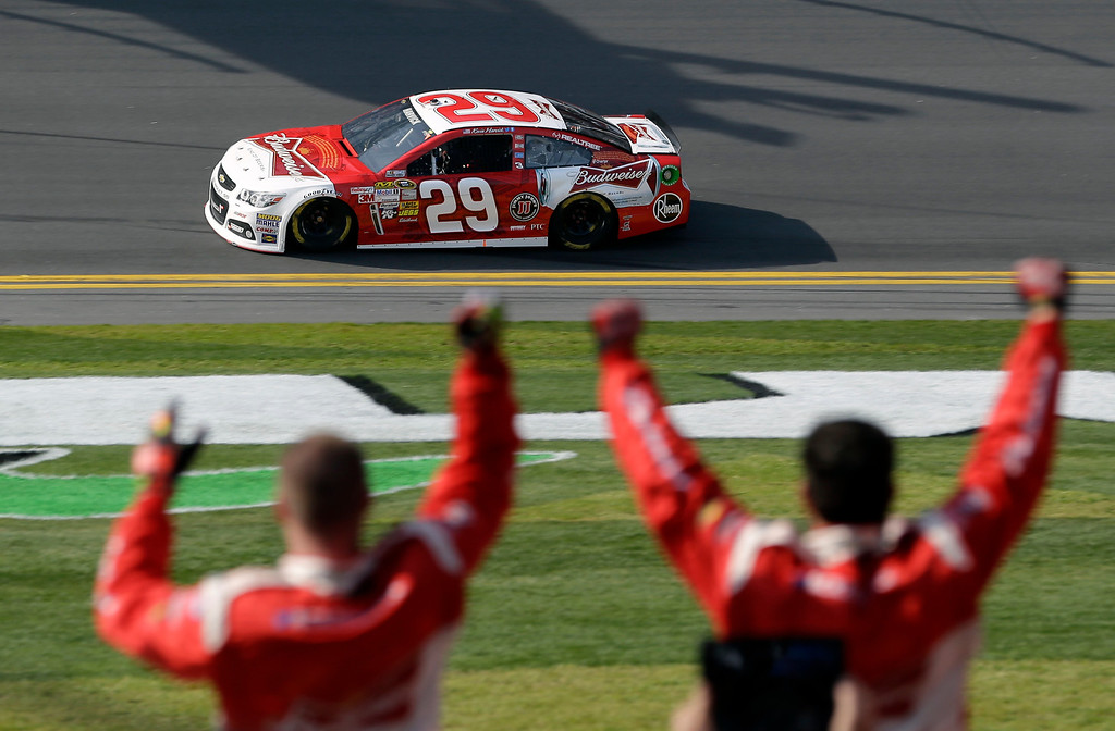 Description of . Crew members from Kevin Harvick\'s team cheer as he heads to the finish line to win the first of two 150-mile qualifying races for the NASCAR Daytona 500 auto race at Daytona International Speedway, Thursday, Feb. 21, 2013, in Daytona Beach, Fla. (AP Photo/John Raoux)