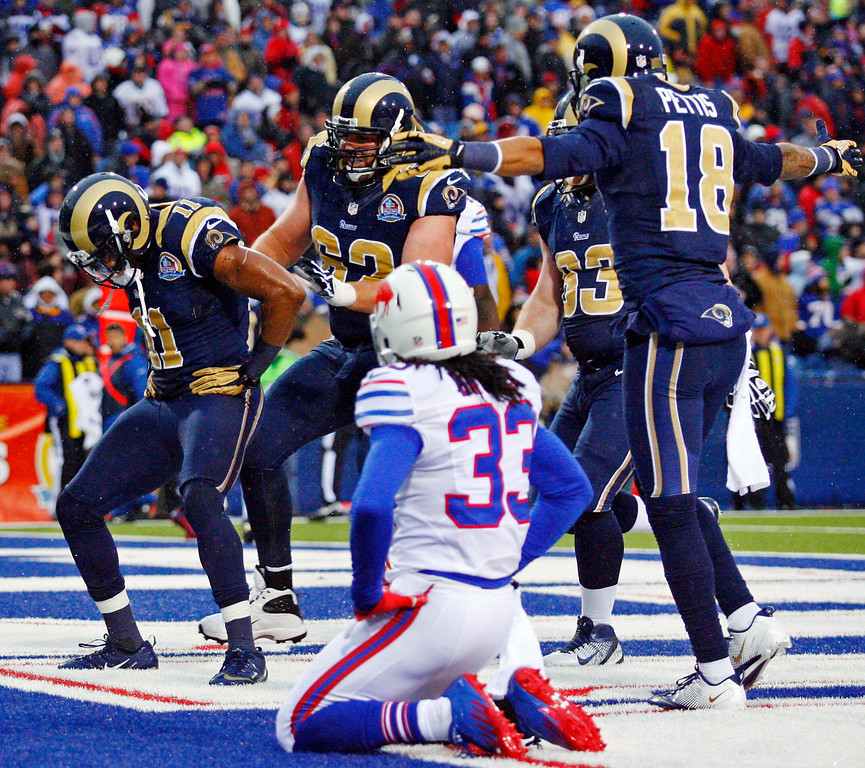 Description of . St. Louis Rams wide receiver Brandon Gibson (11) celebrates with teammates including guard Harvey Dahl (62) and wide receiver Austin Pettis (18) after catching a touchdown pass from quarterback Sam Bradford, not pictured, as Buffalo Bills cornerback Ron Brooks (33) reacts during the second half of an NFL football game, Sunday, Dec. 9, 2012, in Orchard Park, N.Y. The Rams won 15-12. (AP Photo/Bill Wippert)