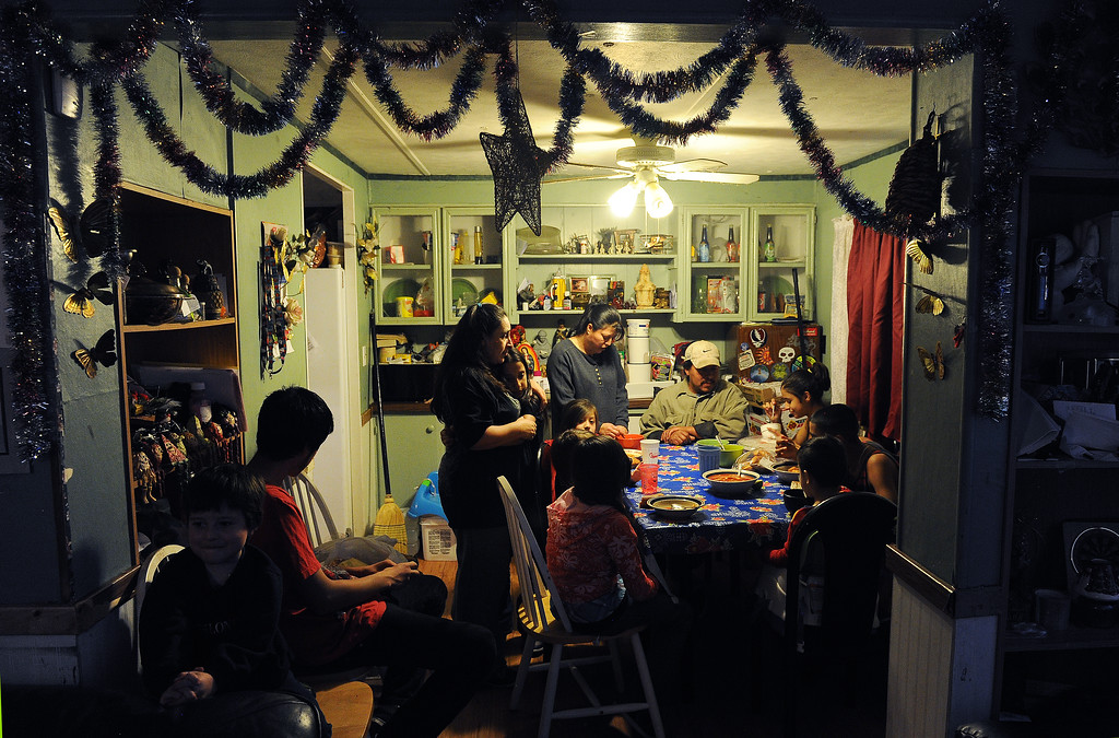 Description of . GREELEY, CO - DECEMBER 16, 2013:  Norma Meza hugs her daughter Maria, 11, as Rosario Moreno, standing, and her husband Jose, seated, join some of the kids for dinner at the Meza's tiny home in Greeley, CO on December 16, 2013. The children seated at the table are from far right  clockwise:  Genoveva Meza, 14, Martin Meza jr., 17, Sergio Meza, 3, Janeth Moreno, 10, Edwin Moreno, 2, Yanna Moreno, 8.  At left are brothers Jared, 5, and Ivan, 18, Moreno. The Meza family, which consists of four children, Norma and her husband Martin have taken in the Moreno family after they lost everything in the September floods.  Rosario and her husband Jose have 5 children and are without a home at the moment.  Norma says she will help out her best friend for as long as she needs to.  The tiny house has 3 bedrooms and 2 small bathrooms and is home now to 14 people, 2 cats and 3 dogs.  (Photo By Helen H. Richardson/ The Denver Post)