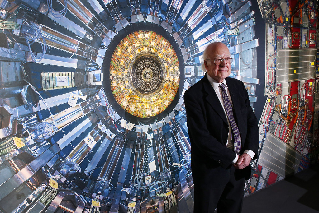 Description of . Professor Peter Higgs stands in front of a photograph of the Large Hadron Collider at the  Science Museum's 'Collider' exhibition on November 12, 2013 in London, England. (Photo by Peter Macdiarmid/Getty Images)
