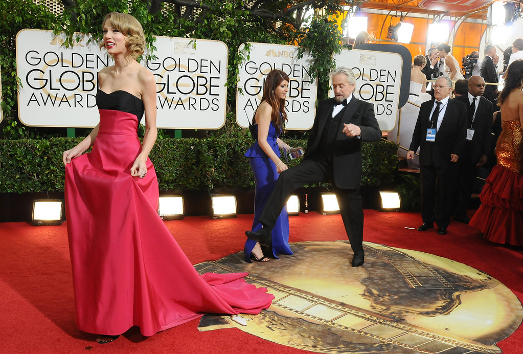 Description of . Taylor Swift, left, and Michael Douglas arrive at the 71st annual Golden Globe Awards at the Beverly Hilton Hotel on Sunday, Jan. 12, 2014, in Beverly Hills, Calif. (Photo by Jordan Strauss/Invision/AP)