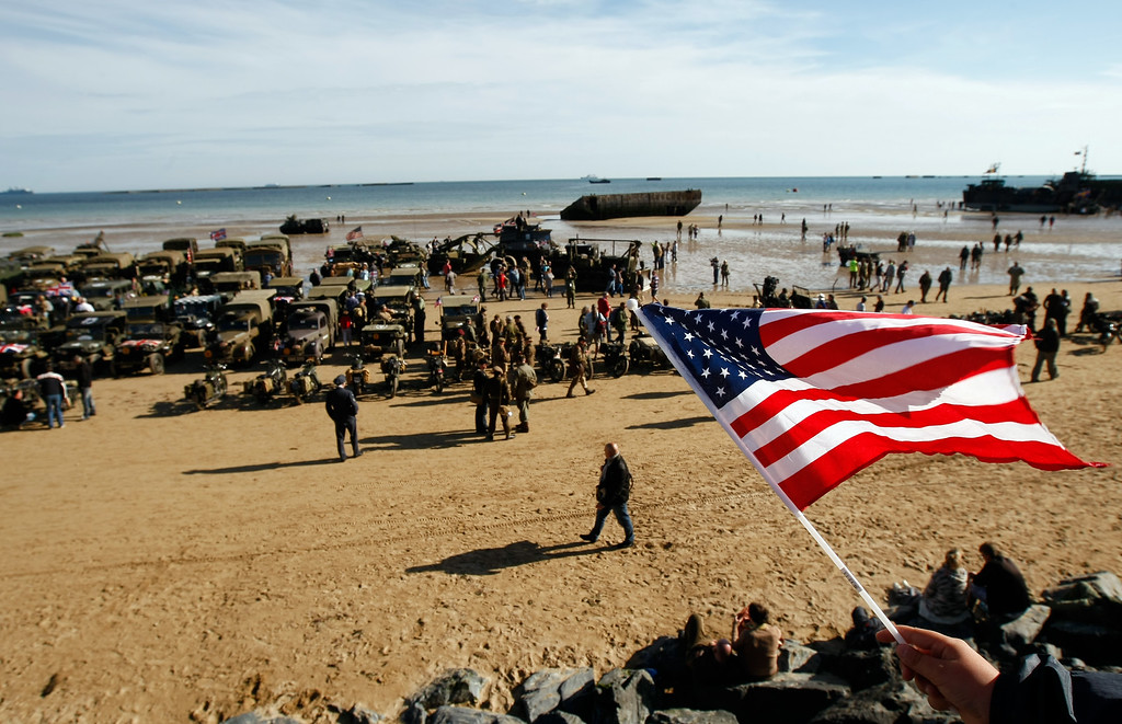 Description of . An onlooker waves an American flag as World War II military vehicles are displayed on the beach of Arromanches, France, Friday, June 6, 2014, as part of D-Day commemorations. World leaders and veterans gathered by the beaches of Normandy, northern France, on Friday to mark the 70th anniversary of the World War II D-Day landings. (AP Photo/Claude Paris)
