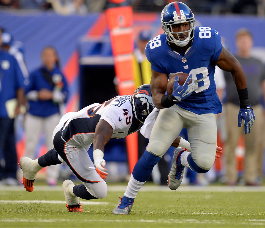 Description of . New York Giants wide receiver Hakeem Nicks (88) picks up a few yards and is caught by Denver Broncos cornerback Dominique Rodgers-Cromartie (45) during the second quarter September 15, 2013 MetLife Stadium. (Photo by John Leyba/The Denver Post)