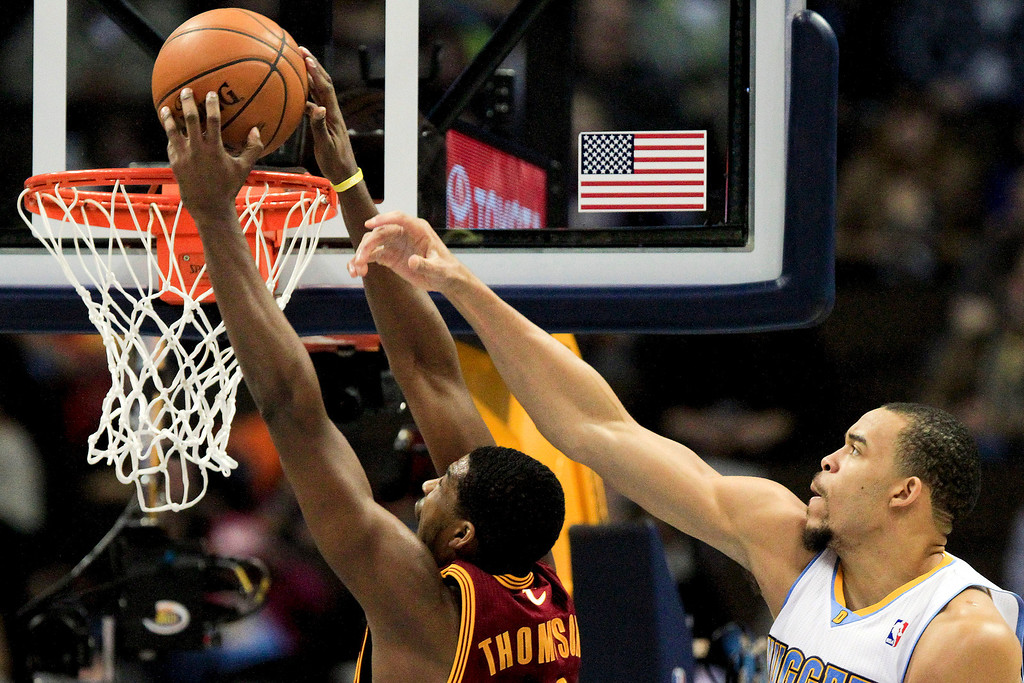 Description of . Cleveland Cavaliers power forward Tristan Thompson, left, scores past Denver Nuggets'  JaVale McGee, right, during the first quarter of an NBA basketball game Friday, Jan. 11, 2013, in Denver. (AP Photo/Barry Gutierrez)