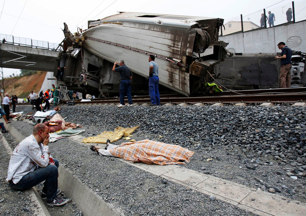 Description of . A picture taken on July 24, 2013 shows An injured man sits next to the body of a victim of a train accident near the city of Santiago de Compostela, Spain. The train hurtled off the tracks, killing at least 78 passengers and injuring more than 140 in the country's deadliest rail disaster in more than 40 years.   MONICA FERREIROS,XOAN A. SOLER/AFP/Getty Images
