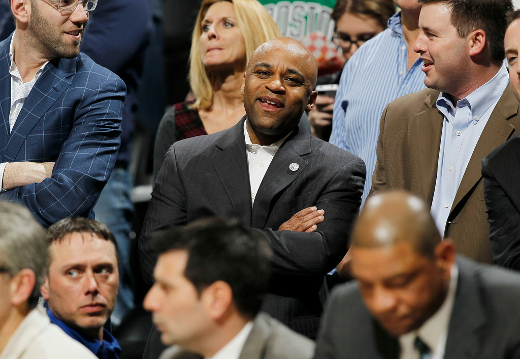 Description of . Denver Mayor Michael Hancock, center, jokes with fans while watching the Denver Nuggets play the Boston Celtics in the first quarter of an NBA basketball game in Denver on Tuesday, Feb.19, 2013. (AP Photo/David Zalubowski)