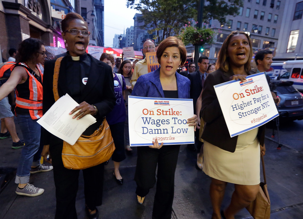 Description of . New York City Council Speaker and mayoral candidate Christine Quinn, center, accompanied by Minister Patricia Malcolm, left, and New York City Council member and public advocate candidate Letitia James, lead a fast food workers' protest march on New York's Fifth Avenue, Thursday, Aug. 29, 2013.  (AP Photo/Richard Drew)