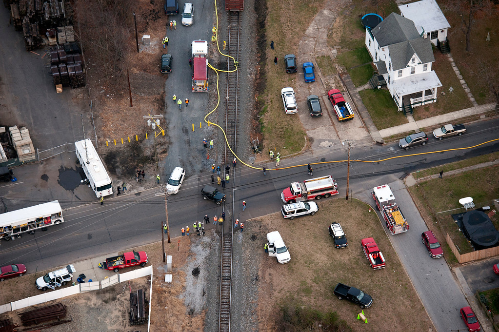 . Emergency personnel respond to an intersection close to where a  freight train derailed in Paulsboro, N.J., Friday, Nov. 30, 2012. People in three southern New Jersey towns were told Friday to stay inside after the freight train derailed and several tanker cars carrying hazardous materials toppled from a bridge and into a creek. (AP Photo/Cliff Owen)