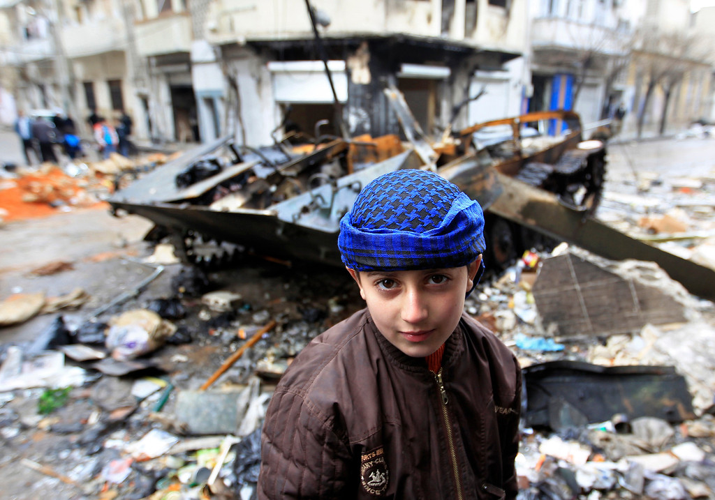 Description of . A Syrian boy stands in front of a damaged armored vehicle belongingREUTERS/Ahmed Jadallah
