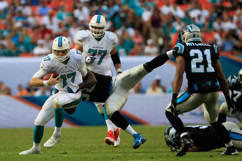 Description of . Ryan Tannehill #17 of the Miami Dolphins is tackled by Thomas Davis #58 of the Carolina Panthers at Sun Life Stadium on November 24, 2013 in Miami Gardens, Florida.  (Photo by Chris Trotman/Getty Images)