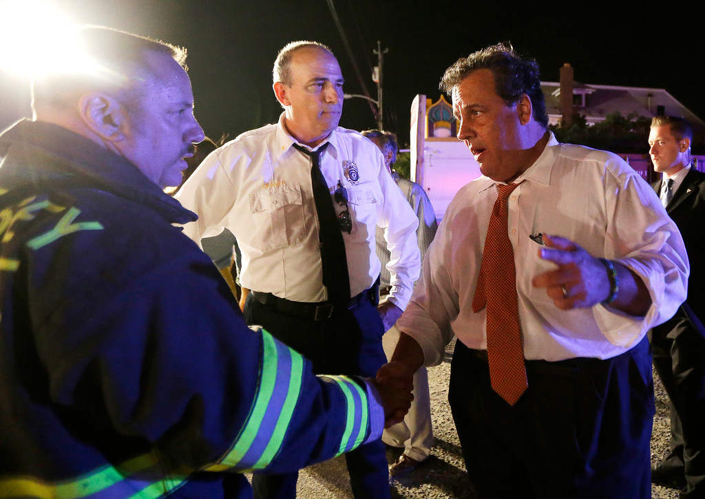 Description of . New Jersey Gov. Chris Christie, right, talks to state fire marshal Bill Kramer, center, and shore regional fire coordinator Craig Augustoni during a visit to the area hit by a massive fire at the Seaside Park boardwalk, Thursday, Sept. 12, 2013, in Seaside Park, N.J. The fire, which apparently started in an ice cream shop and spread several blocks, hit the recently repaired boardwalk, which was damaged last year by Superstorm Sandy. There were no other early reports of any injuries. (AP Photo/Julio Cortez)