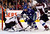 Vancouver Canucks' Alexandre Burrows (C) is stopped by Colorado Avalanche goaltender Semyon Varlamov (L) and Ryan O'Byrne (R) during the first period of their NHL hockey game in Vancouver, British Columbia January 30, 2013.   REUTERS/Ben Nelms