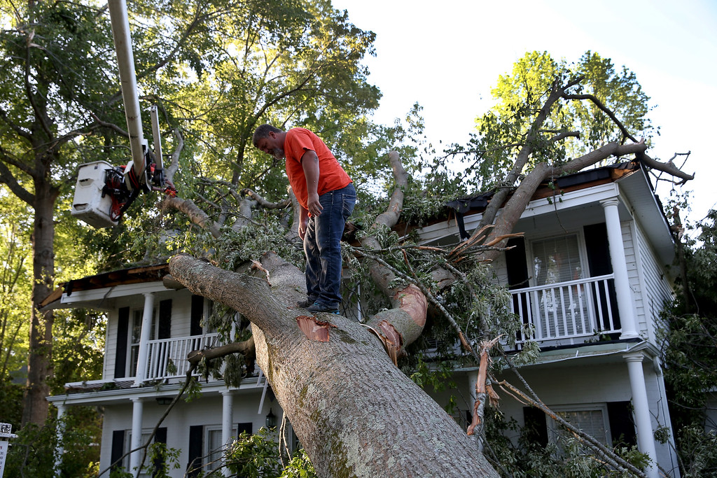Description of . Rodney Stanford from Brewer Tree Service works on removing a tree that is resting on a home after a tornado struck on Monday, on April 30, 2014 in Tupelo, Mississippi.  Deadly tornadoes ripped through the region over the last few days, leaving more than a dozen dead.  (Photo by Joe Raedle/Getty Images)